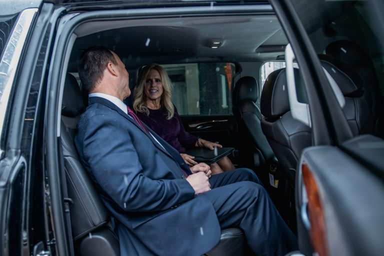 Couple Sitting in Cadillac Escalade Corporate Travel Service by Avant Garde Limousines