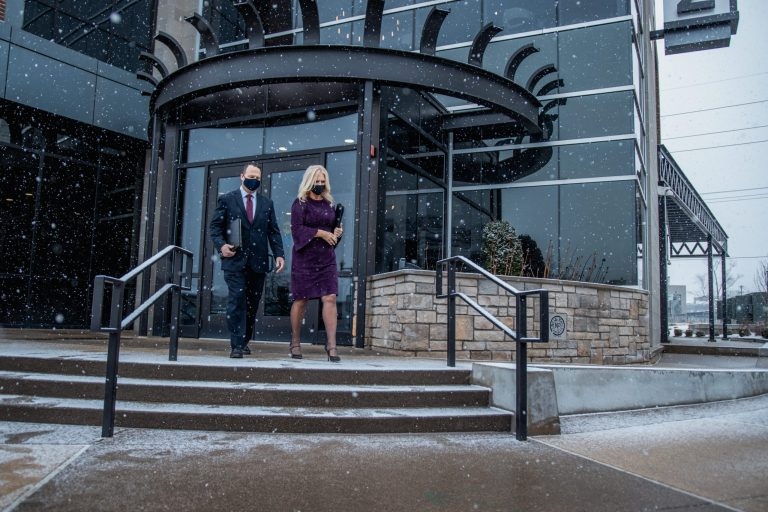 Couple Exiting Building Corporate Travel Service by Avant Garde Limousines