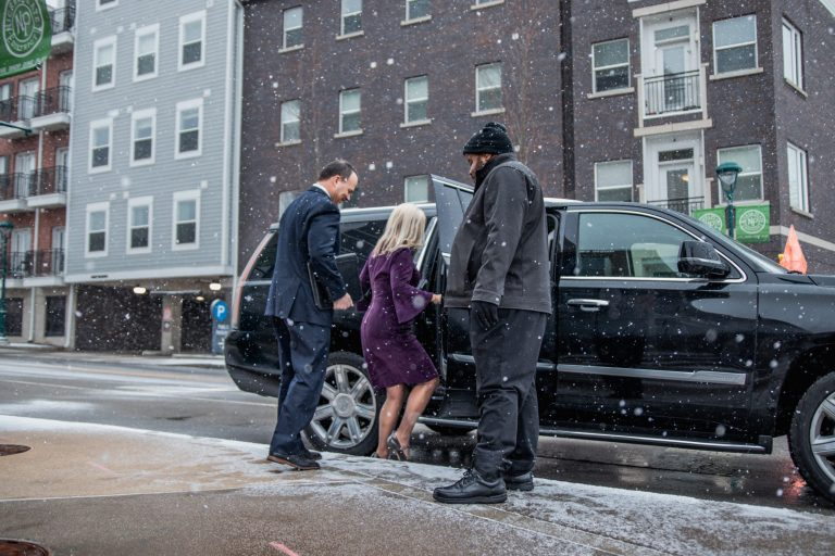 Couple Entering Cadillac Escalade from Avant Garde Limousines for Corporate
